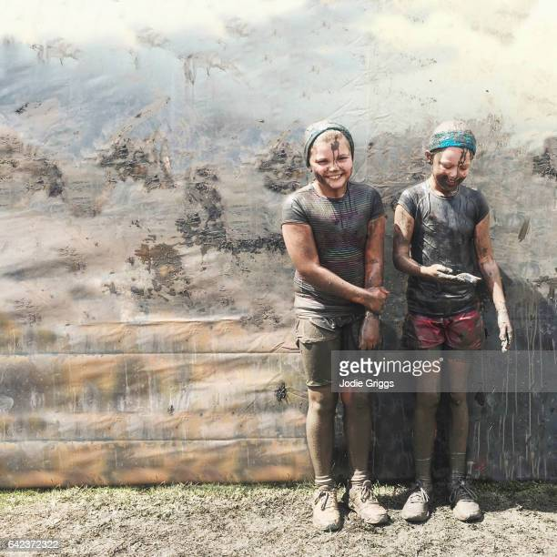 Two happy young girls standing together after completing a mud run challenge