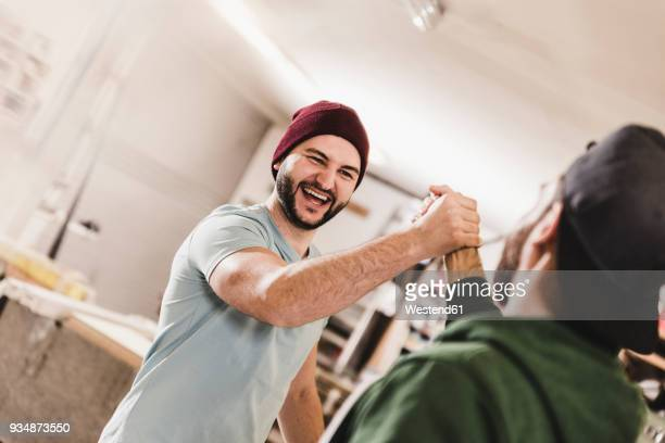 two happy young men high fiving in workshop - high five stock-fotos und bilder