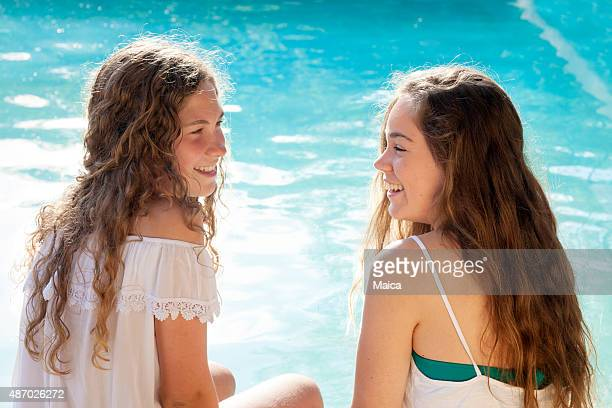 Two happy young woman in the swimming pool