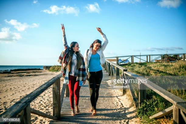 Two happy young woman walking barefoot on boardwalk