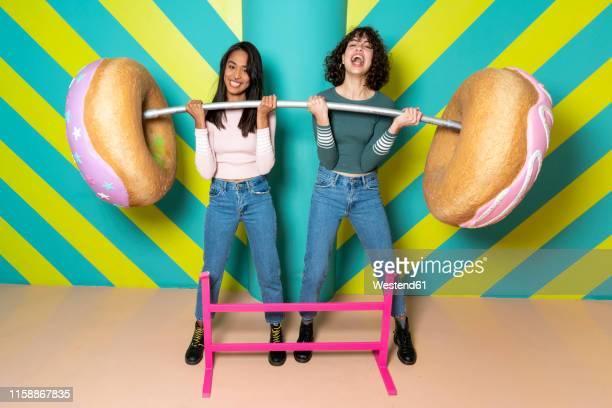 two happy young women at an indoor theme park having fun with oversized donuts - levantamento de peso imagens e fotografias de stock