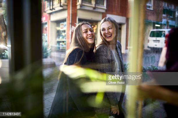 two happy young women behind shop window - consumerism stock pictures, royalty-free photos & images