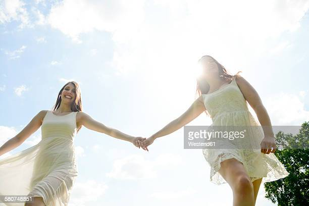 Two happy young women hand in hand
