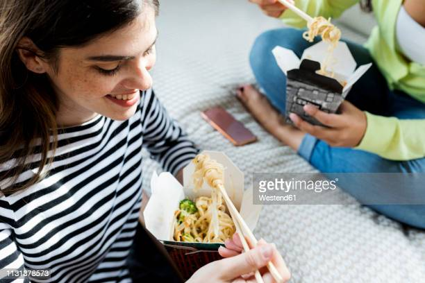 two happy young women having asian takeaway food at home - chinese takeout stock pictures, royalty-free photos & images