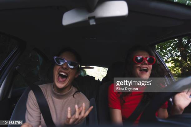 two happy young women having fun in car - cantare foto e immagini stock