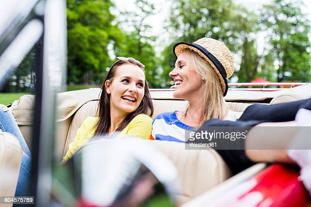 Two happy young women in a convertible