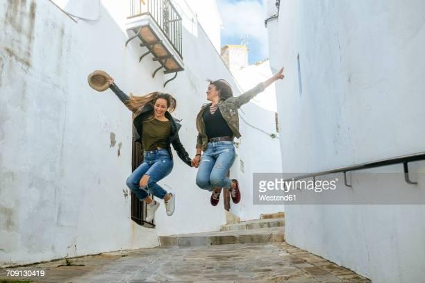 two happy young women jumping in an alley of a town - pueblo fotografías e imágenes de stock