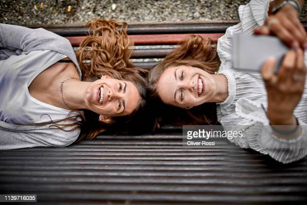 two happy young women lying on a bench using cell phone - due persone foto e immagini stock