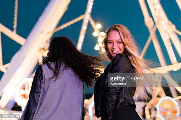 Two happy young women on a funfair at night