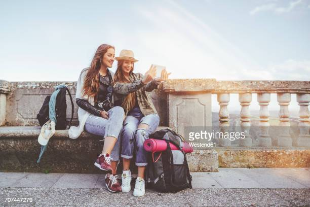 two happy young women on a trip taking a selfie with a tablet - europa locais geográficos imagens e fotografias de stock