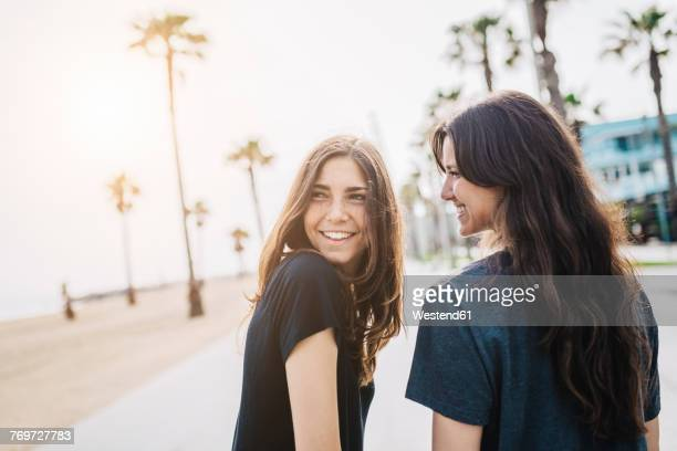 two happy young women on boardwalk - girlfriend stock pictures, royalty-free photos & images