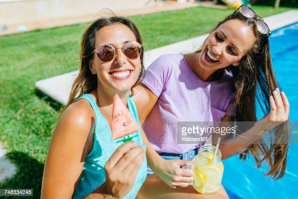 two happy young women with drink and watermelon at the poolside - ritemprarsi foto e immagini stock