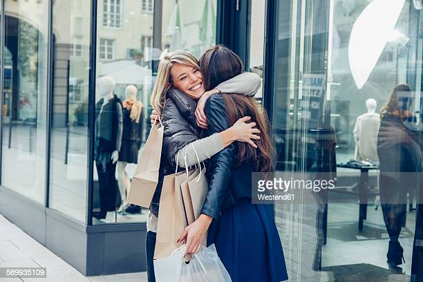 Two happy young women with shopping bags hugging outside a store