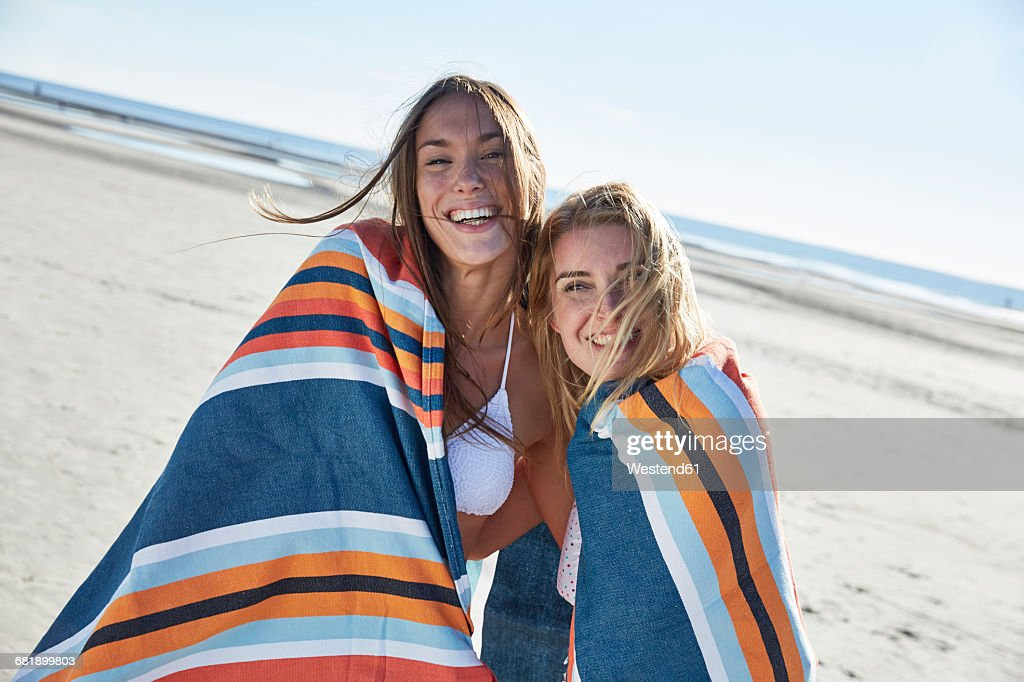 Two happy young women wrapped in a blanket on the beach : Stock-Foto