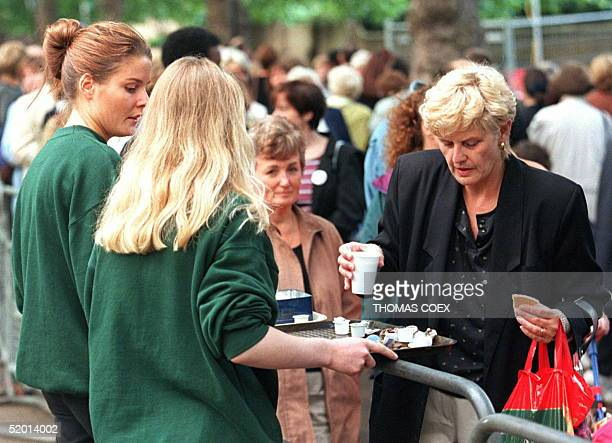 Two Harrods department store employees distribute coffee to women mourners who are among the hundreds who are queueing for up to 11 hours outside St...