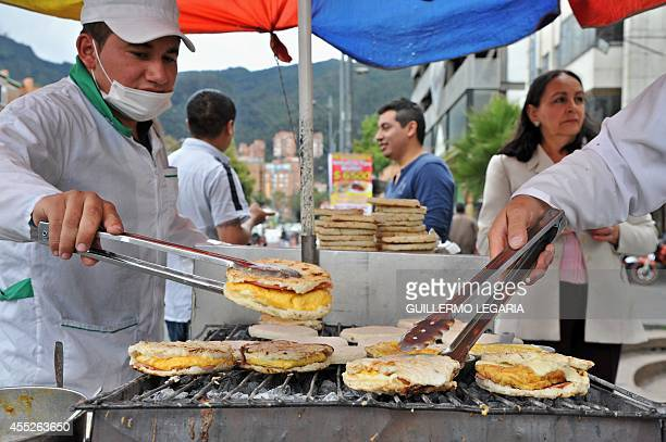 Two hawkers make arepas with eggs at their stall on a street of Bogota on September 4 2014 Many people start early in the morning to earn their...