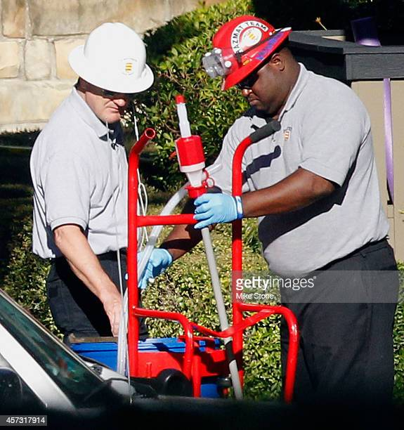 Two hazmat workers insert a pump into a barrel at The Village Bend East apartment complex where a second healthcare worker who has tested positive...
