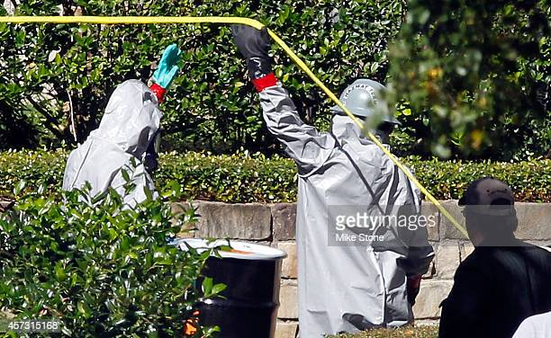 Two hazmat workers prepare to enter The Village Bend East apartment complex where a second health care worker who has tested positive for the Ebola...