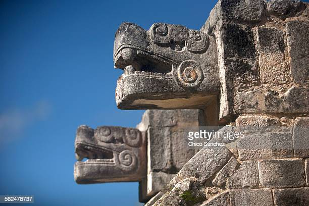 two heads representing kukulkan, the feathered serpent god, decorate a building in the mayan city of chichen itza, yucatan peninsula, mexico - deus imagens e fotografias de stock
