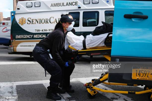 Two health workers lift a patient in to a hospital at Mount Sinai Beth Israel hospital on April 02 2020 in New York City Hospitals in New York City...