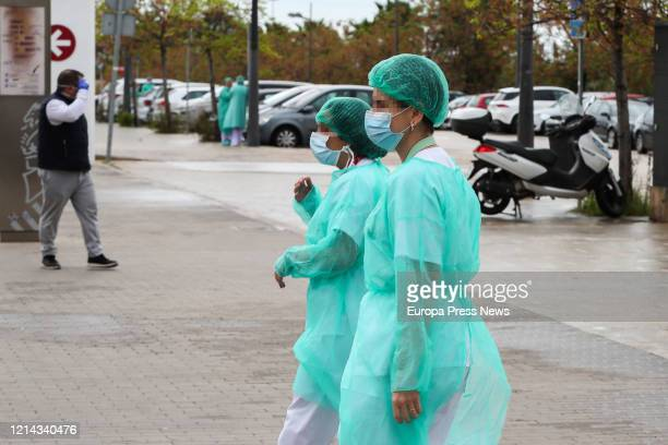 Two health workers protected by a suit, mask and cap, walk near La Fe Hospital and the area where a field hospital is being built to care for...