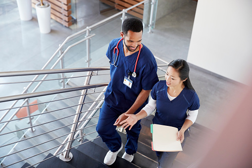 Two healthcare colleagues talking on the stairs at hospital 998342178