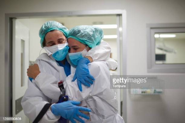 two healthcare workers hug in celebration of a successful surgery procedure - embracing stock pictures, royalty-free photos & images