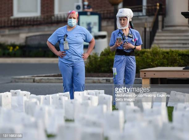 Two healthcare workers in PPE look at the memorial outside the hospital. At the Reading Hospital in West Reading, PA Thursday evening April 8, 2021...