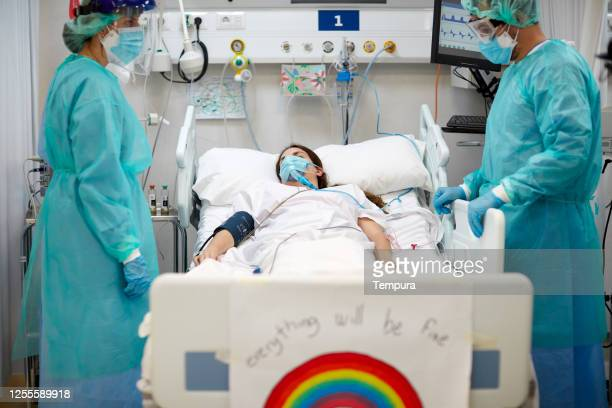 two healthcare workers look in despair at a patient. - intensive care unit stock pictures, royalty-free photos & images