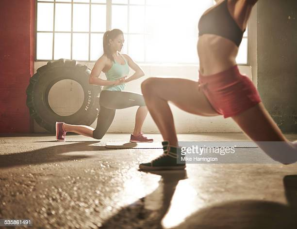 Two healthy females lunging in industrial gym