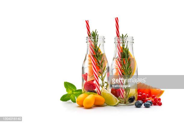 two healthy infused fruits water detox bottles isolated on white background. copy space - infused water stock pictures, royalty-free photos & images