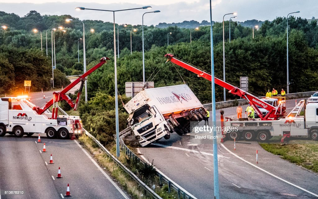 Two heavy lifting Mansfield rescue trucks lift a German articulated Hamburg Sud truck that fell on its side crushing a blue van while exiting the M20 motorway at Junction 8 travelling south to the A20. The accident happened at about 17:30 with the truck being lifted at 21:30 on Wednesday July 12, 2017 in Maidstone, England.