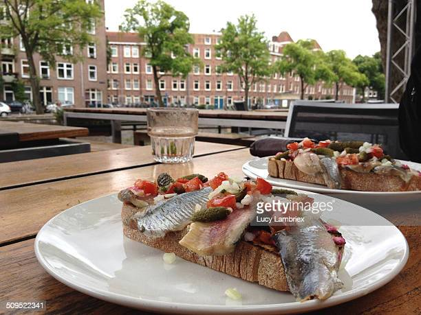 Two herring sandwiches on a terrace table