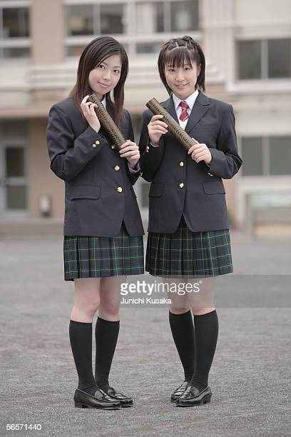 Two high school girls holding graduation certificates