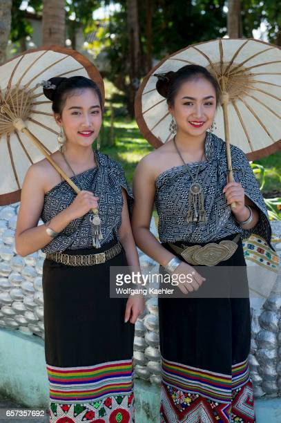 Two high school girls in traditional dresses and with parasols posing on the staircase of a temple in the UNESCO world heritage town of Luang Prabang...