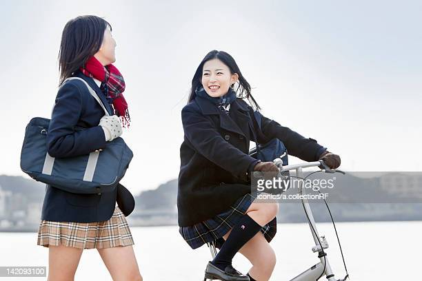 Two high school girls walking and cycling