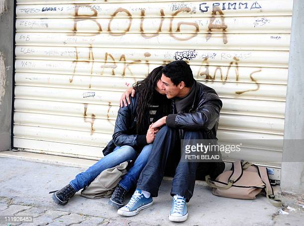 Two high school students kiss outside their high school in Carthage presidency in Tunis on February 25 2011 AFP PHOTO / FETHI BELAID Tens of...