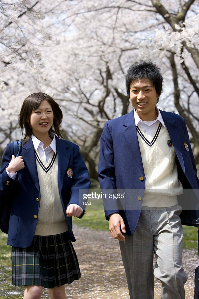 Two High School Students on Path with Cherry Blossoms in the Background : Photo