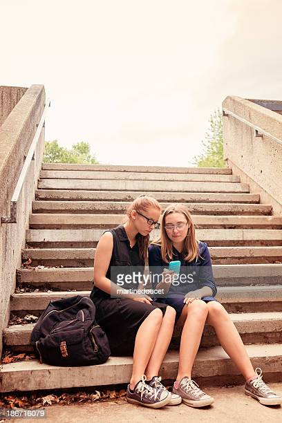 Two high school teenagers texting on staircase.