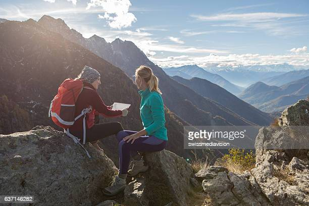 Two hiker females using digital tablet on mountain top