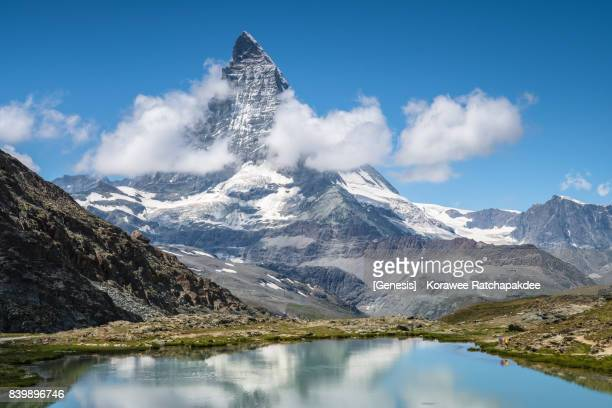 A two hiker hiking at the Matterhorn hiking route in the summer season with beautiful landscape and reflection of Matterhorn, Jul 13,2017, Zermatt, Switzerland