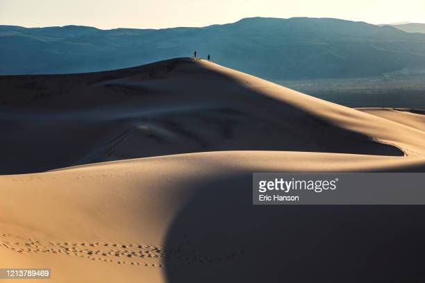 two hikers atop a giant sand dune in death valley - death valley photos et images de collection