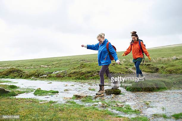 two hikers crossing stream in countryside - dougal waters stock pictures, royalty-free photos & images