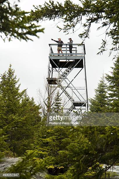 Two hikers enjoy the view atop the observation tower at the Bald Mountain summit in the Rangeley Maine area on Friday May 11 2012