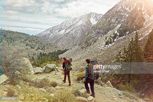 two hikers heading towards distant mountains