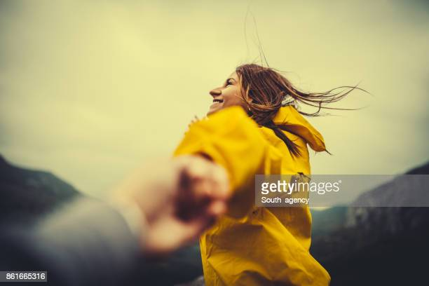 two hikers in nature holding hands - yellow coat stock pictures, royalty-free photos & images