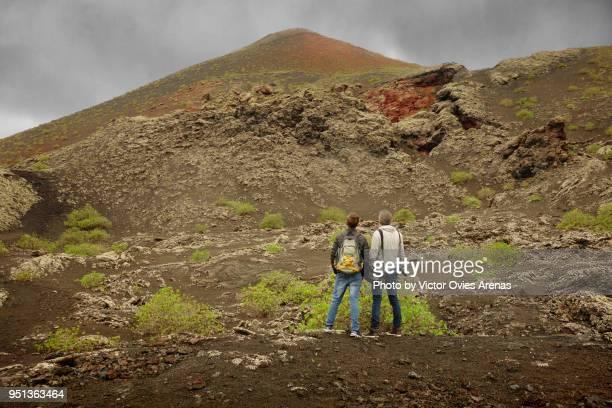 two hikers looking at a volcano peak in timanfaya, lanzarote, canary islands - victor ovies fotografías e imágenes de stock