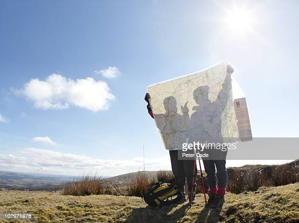 two hikers looking at map - karte navigationsinstrument stock-fotos und bilder