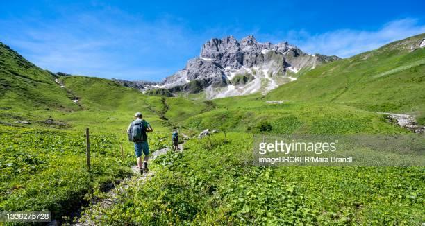 two hikers on a hiking trail, hiking trail to the kemptner hut, in the background rocky mountain peaks of the kratzer, heilbronner weg, oberstdorf, allgaeu, bavaria, germany - weg fotografías e imágenes de stock