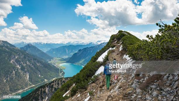 Two hikers on hiking trail, crossing from Seekarspitz to Seebergspitz, view of the lake Achensee, Tyrol, Austria